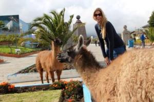Die Moderatorin Frau Schlaumeier amüsiert sich über die Lamas am Mittelpunkt der Erde in Equador.